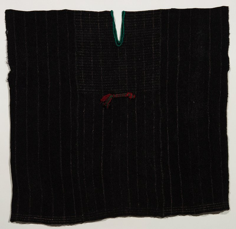 wide black woven huipil woven ona backstrap loom; small green/red braid decoration applied on the front and back; neck slit is edged with green buttonhole stitch