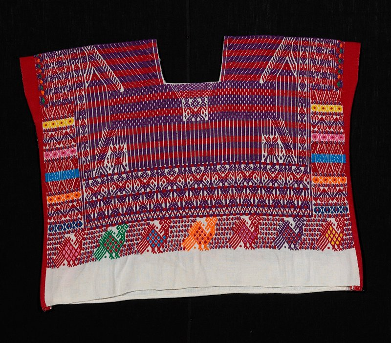 one-paneled white cotton huipil with wide red bands on both sides; zoomorphic and geometric brocaded designs; red, purple, blue, yellow, green, orange, turquoise, pink