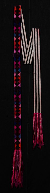embroidery on nearly half of belt in blue, pinks, oranges, and striped vertically on other half in black and beige; many twisted tassels at each end