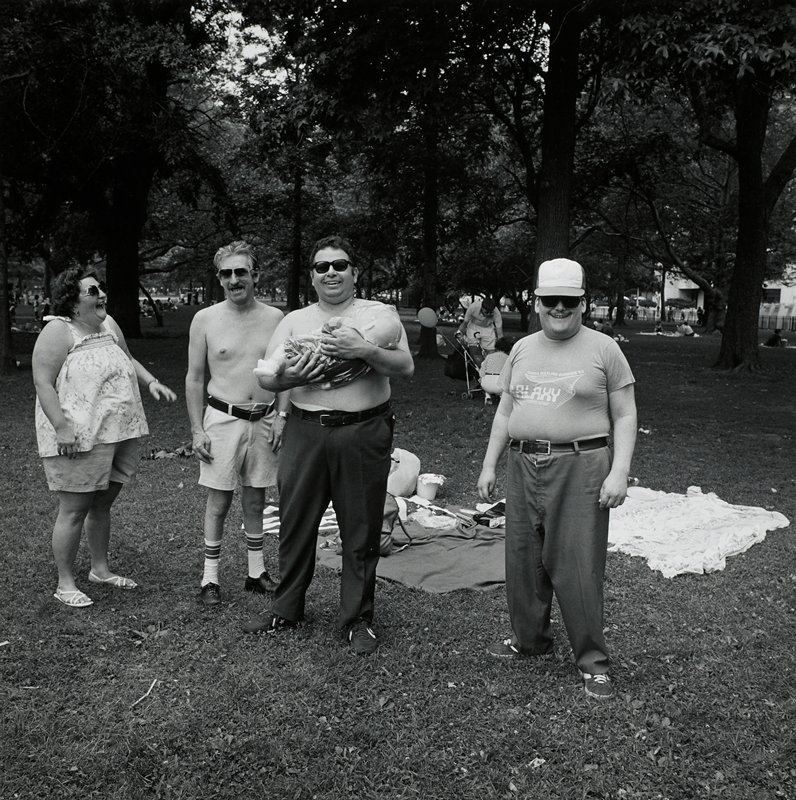 4 figures standing in a park, from left: laughing heavy-set woman wearing a tank top, shorts and sandals; heavy-set shirtless man wearing shorts, tube socks and black shoes; heavy-set shirtless man wearing slacks and tennis shoes, holding a baby doll in a plastic bag; heavy-set man wearing cap, t-shirt, slacks and tennis shoes