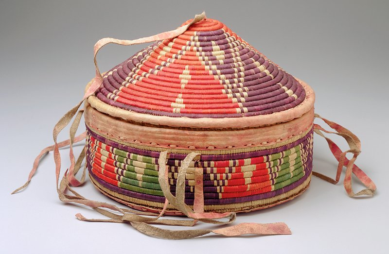 Basket with straight sides; cone-shaped lid; red dyed leather on bottom, at rim of basket and cover and ties; pyramid decorations in purple, red and green dyed fibers