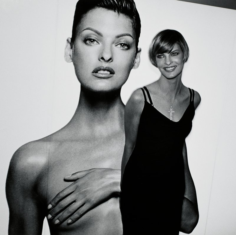Linda Evangelista, wearing a large cross pendant necklace and a black dress with thin straps, standing in front of a large blown-up photo of herself, from head to chest