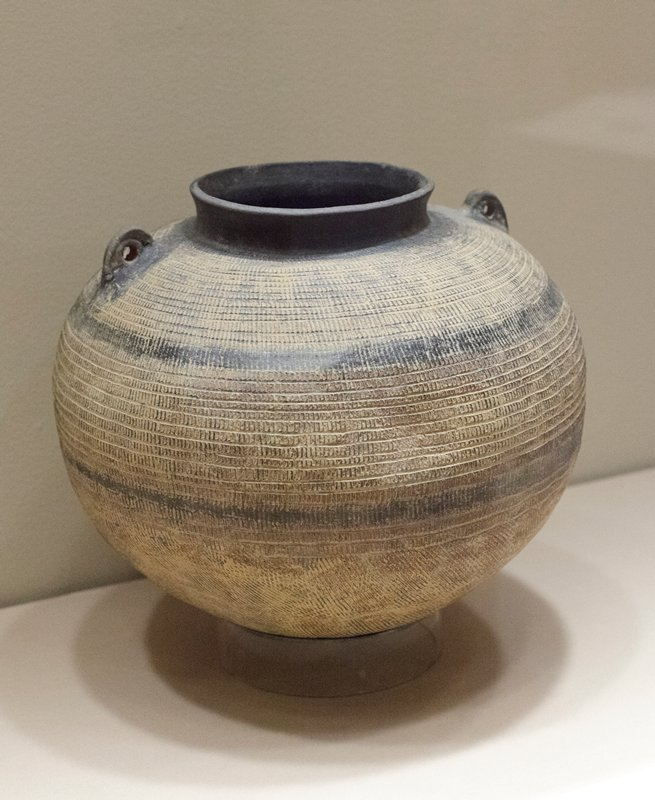 Round base; raised black lip; two black handles with openings on shoulder; horizontal black, brown and tan bands of decoration with vertical incised lines running through them; incised bird print shape on side near bottom; has lidded wooden box