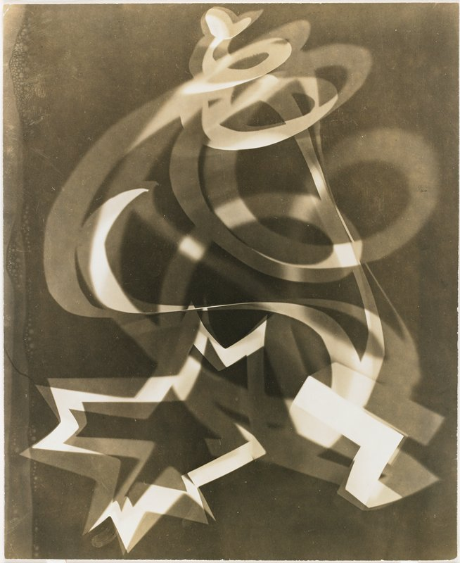 Blurred ribbon shapes of swirls and stars; dark background, extended exposure of a rotating light ribbon; most noticeable shapes include swirls at top center and star-like image at lower left center