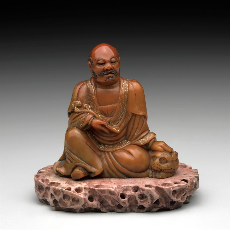 seated man wearing robes trimmed in gold, holding a sceptre in his PR hand and stroking a tiger, emerging from his robes, with his PL hand; orange figure; pink stone base