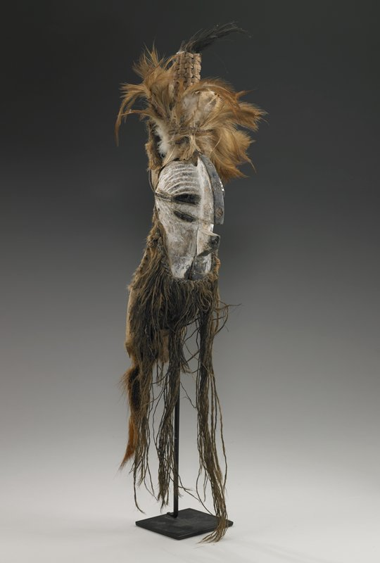 miniature kifwebe mask with prominent median crest; encrusted with kaolin with blackened facial features; long vegetable fiber beard; tall cane and feather topknot; mounted on an animal skin