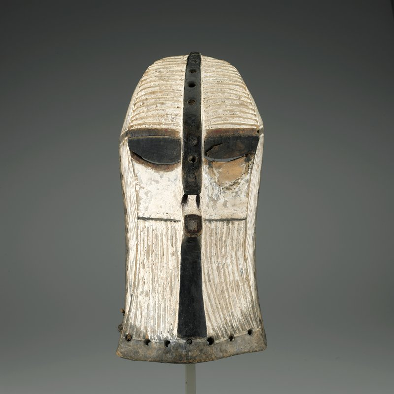 mask carved on flat rectangular planes; median crest and nose drilled at regular intervals with small cavities containing traces of symbolic materials; tufts of hair implanted in nostrils; white and black highlights; intricately grooved surface