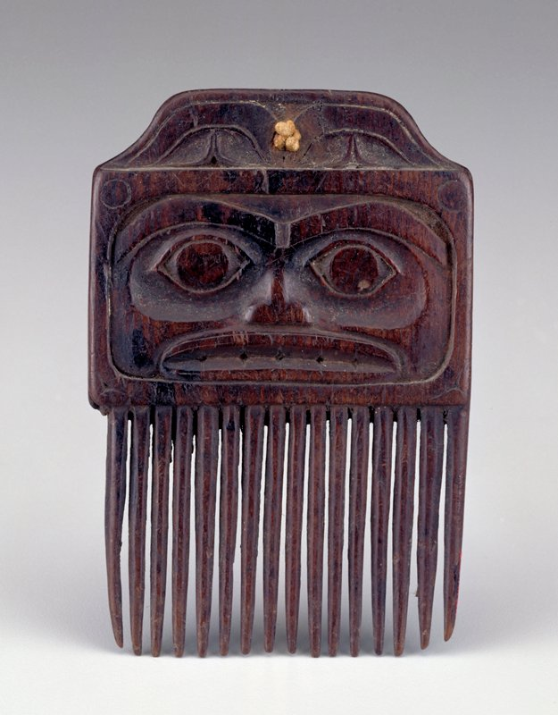 comb topped with face with slightly sunken eye sockets and wide mouth on one side; lightly incised, abstracted face with large round eyes on opposite sides