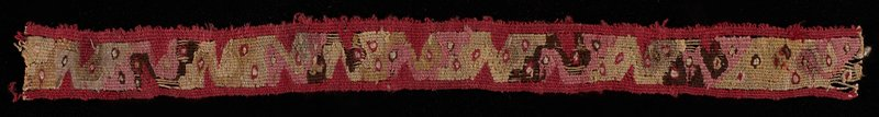 fragment of a border with red, tan, white, pink and brown organic design; mounted between 2 pieces of plexi