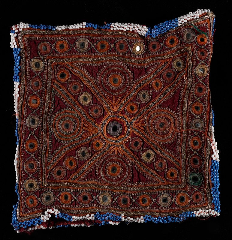 square; edged in blue and white beads; dark red with gold, orange, blue and green embroidery and mirror disks