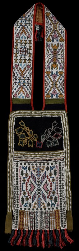 bag with fully beaded pouch, strap and tassels at bottom and at top of strap; black velvet panel beaded with leaf shapes above pouch; blue and red yarn tassels; grey and white striped cloth on back of body