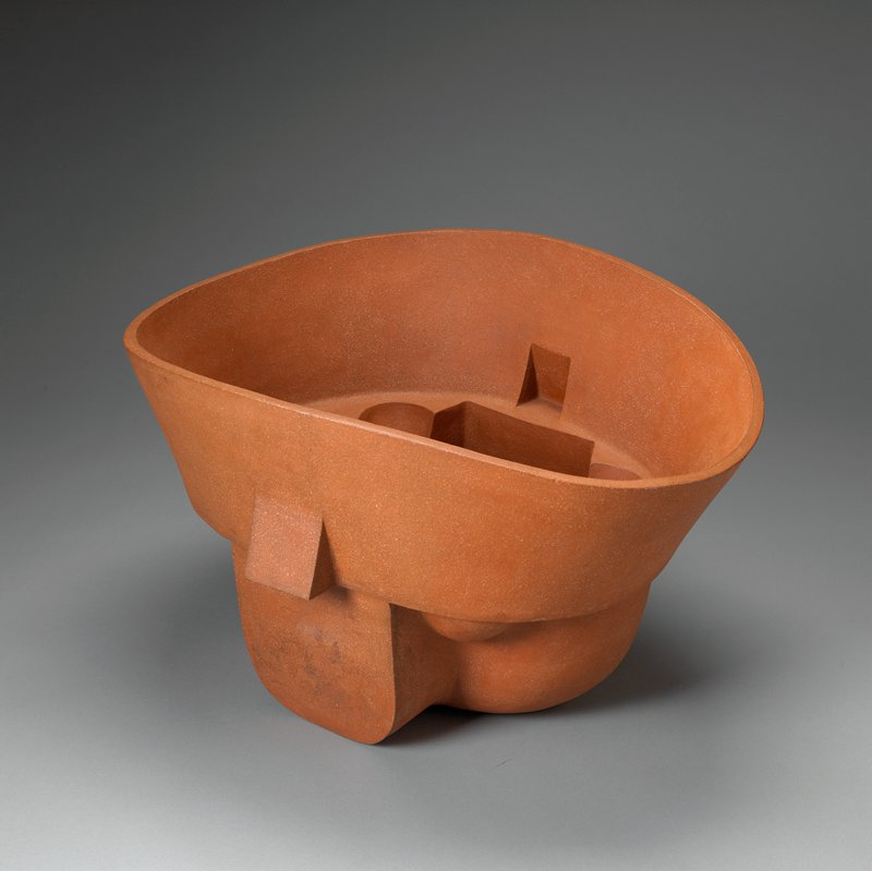 "terra cotta colored deep oval vessel with sharply ""carved"" sides and two ""handles"""
