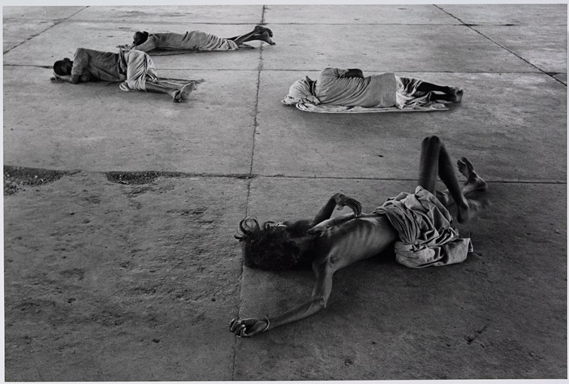 4 people lying on the ground; man in front has long hair and beard and is bare-chested, with prominent ribs