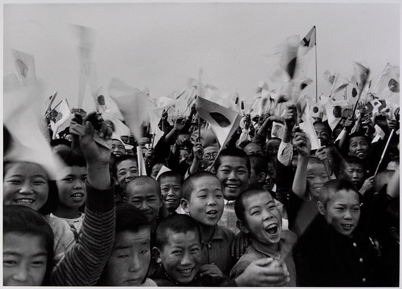 large group of children (mostly boys) smiling and waving small Japanese flags