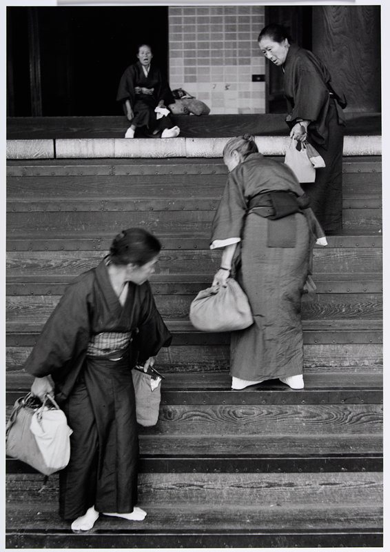 2 women walking up stairs, one woman walking downstairs, one woman seated at top of stairs; each woman wears a kimono and carries cloth bags