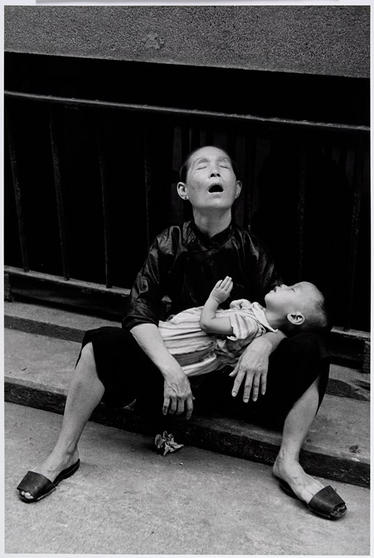 woman seated on a curb, with upraised head, closed eyes and open mouth, holding a sleeping child on her lap