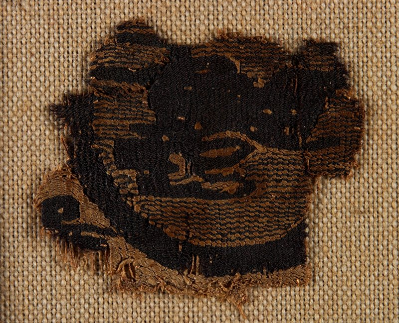 fragment of a medalion surrounding a running animal with long ears in dark brown on tan