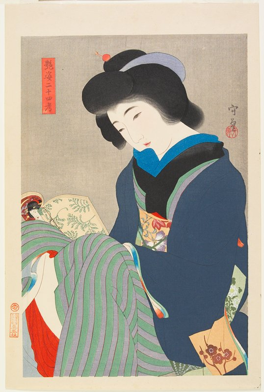 seated woman with knees drawn up, reading a book; blue jacket over green and grey striped kimono