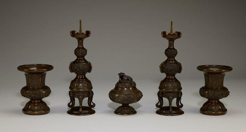 tapering stand; demon heads on bottom; birds in foliage with berries in relief at center; dragon in clouds at top below pointed finial; has storage box for five piece group