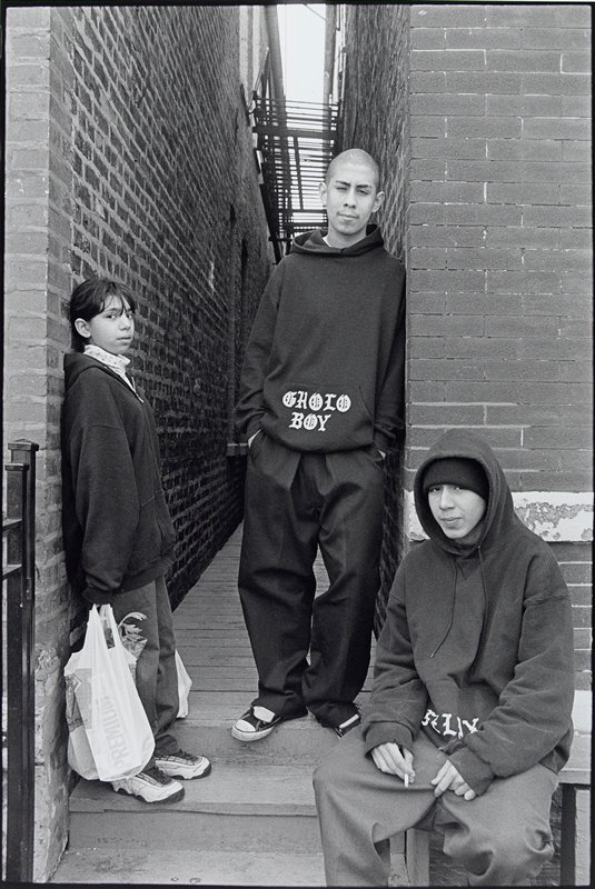 """three figures in front of a narrow wooden walkway between two brick buildings; girl at L wearing zippered sweatshirt and carrying plastic bag; boy with shaved head at center wearing sweatshirt printed, """"GHOLO (?) BOY""""; seated smoking boy at R, wearing sweatshirt printed, """"FELIX"""""""