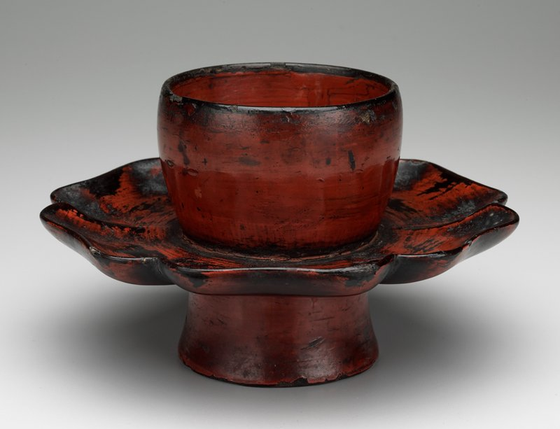 red and black cylindrical shaped stand with attached central saucer; has storage box