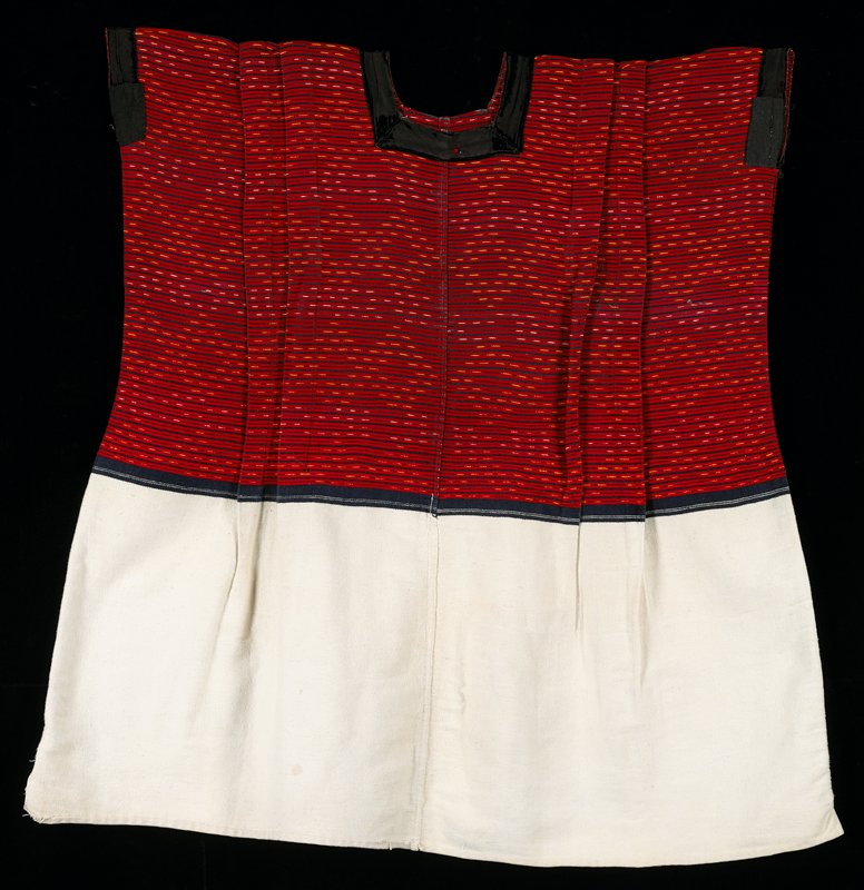 White and red cotton two-panel huipil. Indigo stripes and fine yellow-blue and white blue ikat stripes; black velvet and cotton fabric border at neck and armholes.