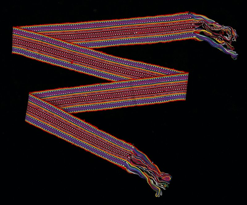 Possibly belongs with 2002.280.52 and 54 as a costume. multicolored striped sash, red, yellow, pink, white, dark and light blue, green black; fringe.