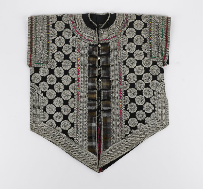 black ground with floral/ rondel design and repeating geometric borders; brown plaid at front opening; five bell-like metal buttons; applique trim with gold threads