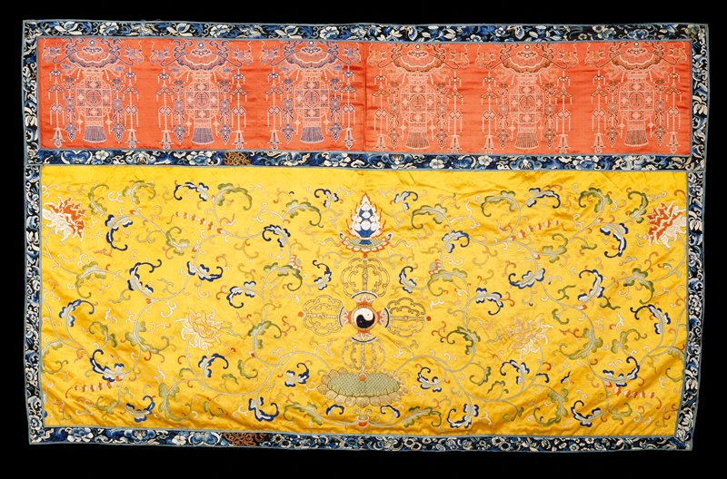 Hanging of embroidered imperial yellow satin with an upper valance of brocaded red satin. The central design of the lower portion shows the Yin and Yang symbol emerging from a lotus flower. In the field on either side are large lotus blossoms and trailing branches. The colors include shades of blue, green, coral, mulberry, pink, yellow and tan. Chiefly satin stitch and couching. The brocaded valance carries a row of hanging lanterns with mystic symbol pendants in shades of brown and tan. Around the edge, and separating valance from main field is a band of black satin embroidered with running floral pattern in shades of blue. Lining of yellow cotton. NoteA.P. thinks brocade may be later than early 18th century.