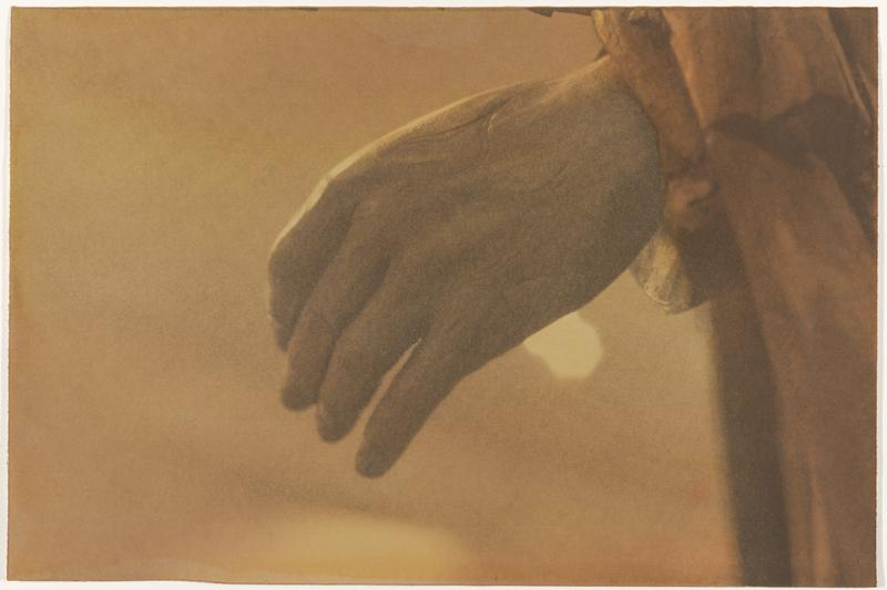 proper left hand with fingers loose and slightly bent, emerging from draperies at right; sepia tone overall