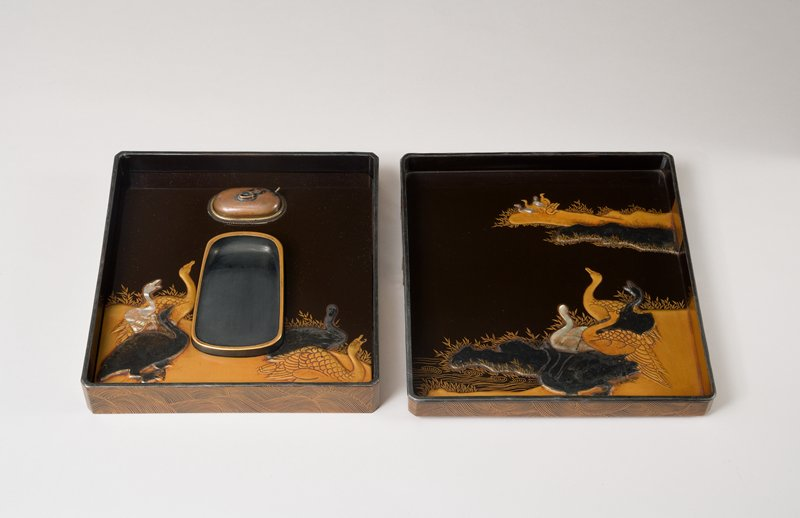 square writing box with golden wave pattern surrounding a bridge with mother-of-pearl supports; inside: pewter, gold, and mother-of-pearl swans on golden bank with eddies; design of swans inside around ink stone
