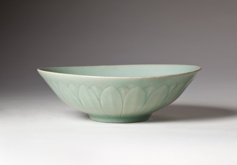 shallow bowl with incised line around inner center; shallow relief lotus petal design on underside; pale blue-green celadon glaze
