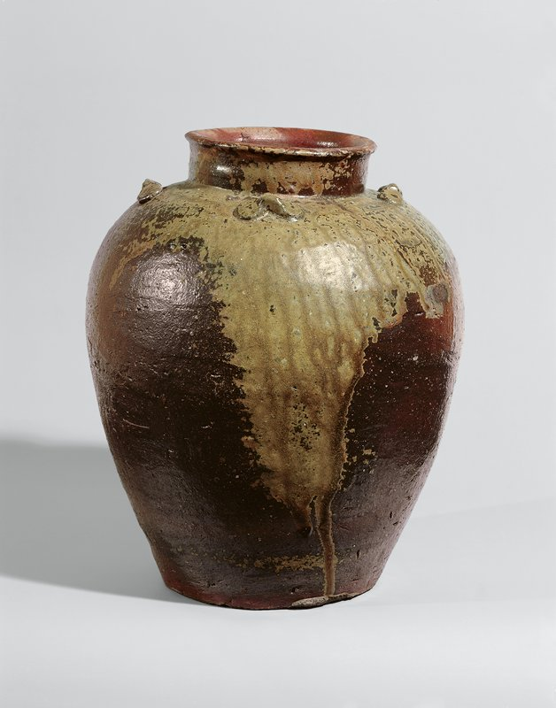 red-brown jar with mottled ochre colored glaze around shoulder and down one side; four bow-like decorations around shoulder; short, vertical neck