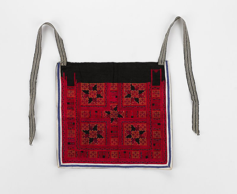predominately red cross-stitching in design with squares and five stars on black; white and blue trim on three sides; black and white woven ties