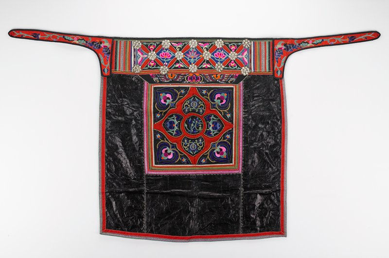 dark blue cotton backing; shiny blue front; embroidered green and pink outer border; central square panel with applique and floral embroidery; wide top band with hammered silver flowers and applique and floral embroidery; short red straps embroidered with birds and flowers