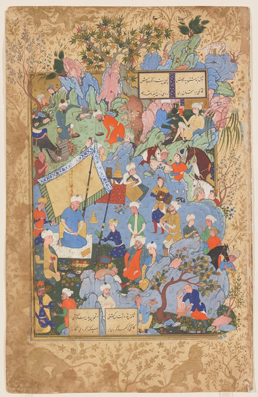 Miniature from a Nizami Manuscript depicting a King on a picnic with an animated group of courtiers in vivid costumes. The scene ia a rocky landscape with flowering shrubs and trees whose branches project into the side and top borders. Two small panels of inscription inset at top right and lower left.