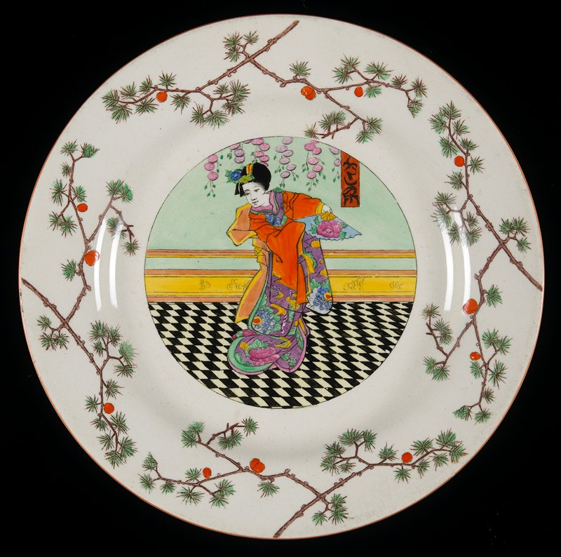 """creamware; orange line rim; shoulder decorated with blossoming pine branches; center painted with """"Ukiyo-e"""" style woman in floral kimono, holding a fan, in an interior with black and white checker-board floor"""