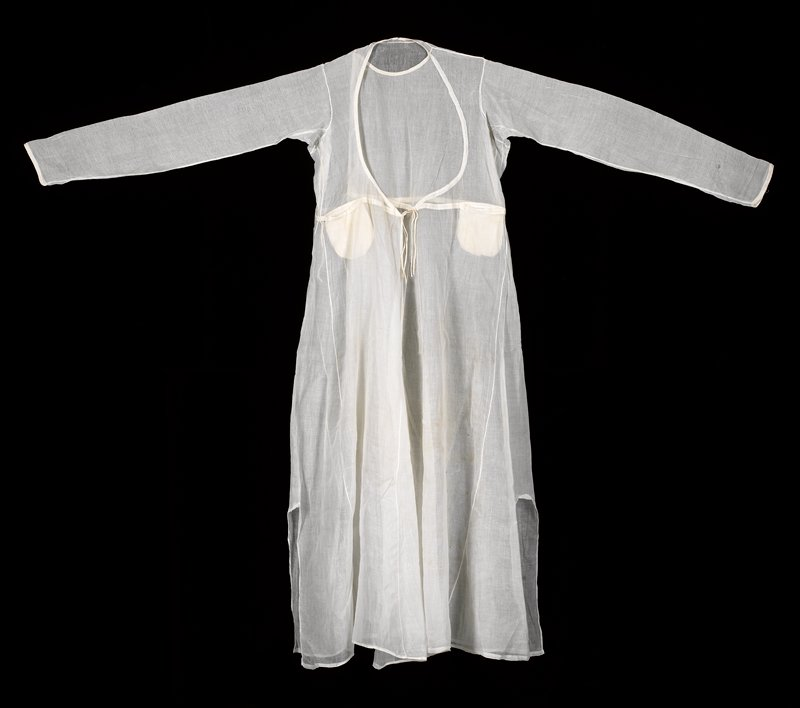 plain ecru cotton (sheer); long sleeves; several panels sewn together, with four braided ties; two pockets on front at waist; small rolled fabric button at neck