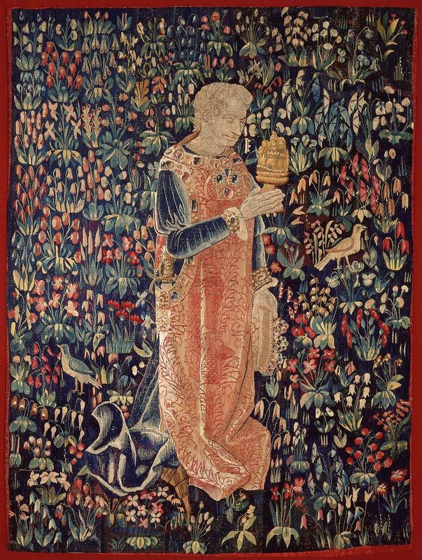 Tapestry. On a mille-fleur ground a knight wearing a sword and a surcoat, probably of velvet, with a design of large flowering pomegranites on a serpentine band. He carries a chalice in his right hand and a jewelled coronet in his left. Plain narrow red border badly worn. Some restoration. Partially lined with white cotton.
