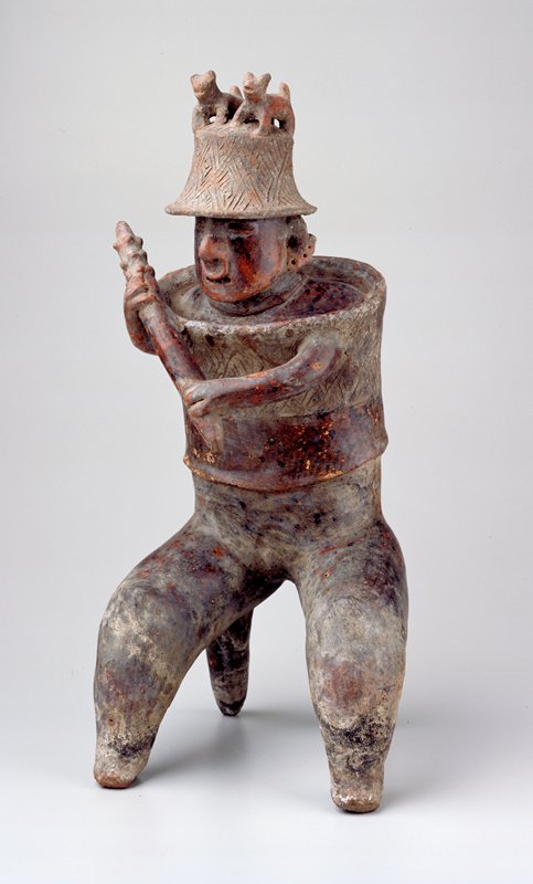 Crouching figure of warrior with two leg-like supports in back. Around the upper body is a shield from which the arms emerge, holding a notched club up to the righ shoulder ready for a strike. Helmet with incised design topped by two standing dogs in full relief. Shield incised with lozenge design. The face is full, with small mouth and eyes, nose plug and ear plugs. Polychrome designe of lower shield and body badly worn. Cracks at right and left center in back.