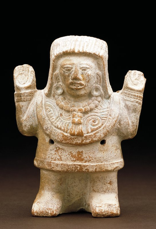 rattle in the form of a man; arms upraised, fingers incised, scroll in each palm; the figure wears a short tunic, heavy breastplate, bracelets, and disk earrings; formal headdress; plain back; four pierced holes, two in front and two in back for rattle sounds; figure made from mould