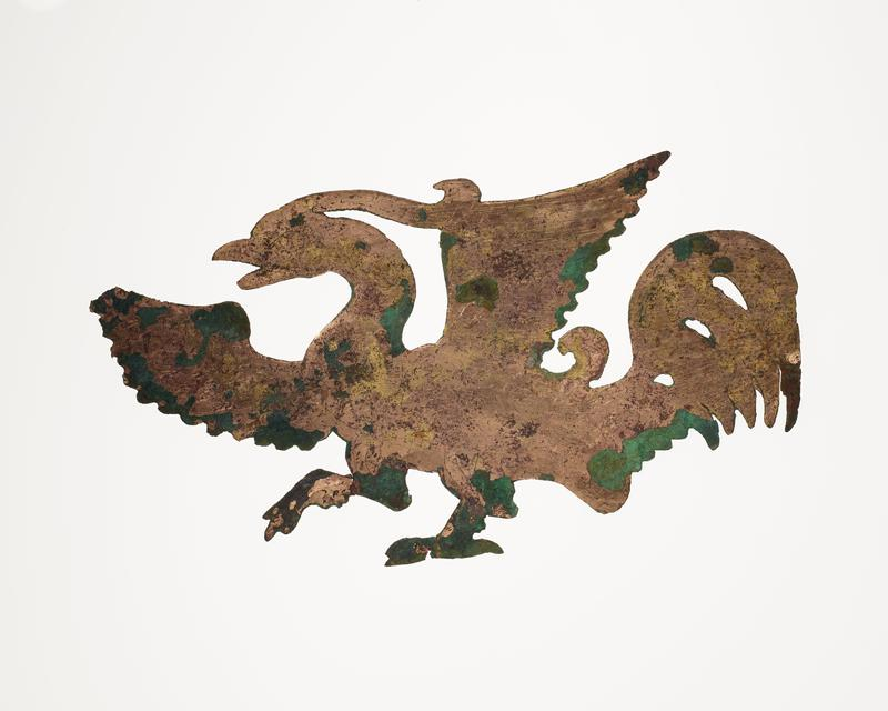 walking bird with wings outstretched; rooster-like tail-feathers; facing L; mounted on black cloth-covered board with L2003.116.7.1, .2
