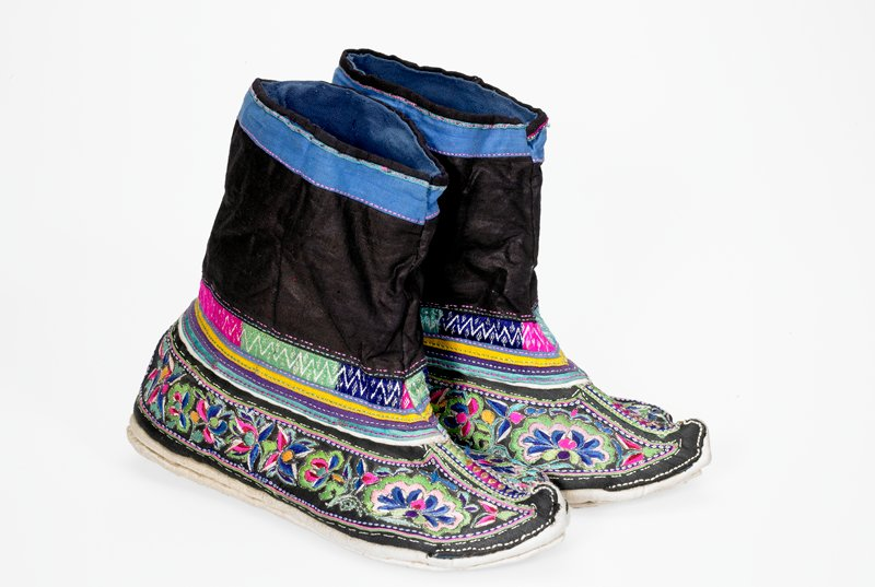 bootie-like shoes with white soles; navy blue ankles with light blue trim; body of shoe black embroidered overall with multicolored flowers; sewn together at collar