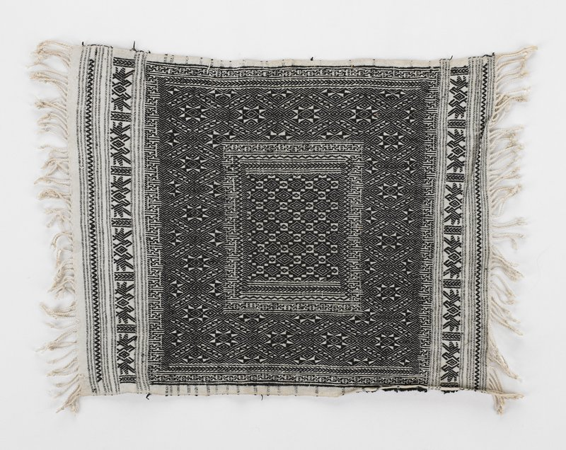white ground; black weaving or embroidery overall in geometric and bird patterns; white fringe