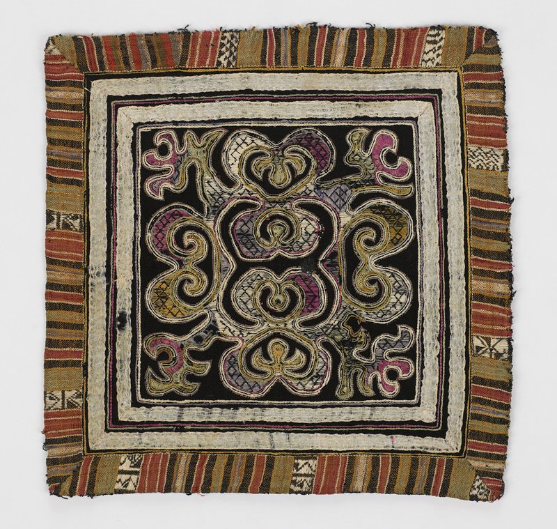 organic design in white, yellow, green, purple and pink on black embroidered at center; white ribbon and striped cloth trim; Surface ornamentation