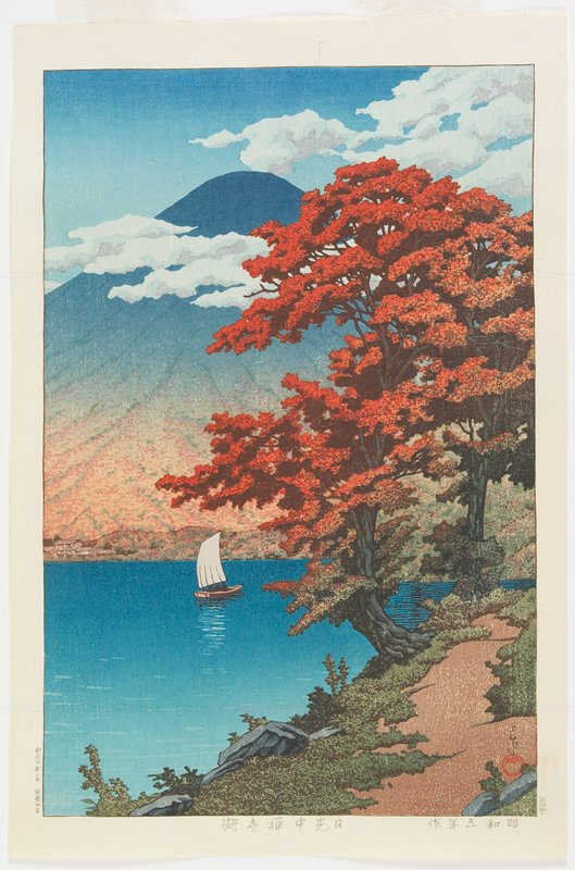 tree with rust colored leaves on shoreline; sailboat in distance; mountain peak in background