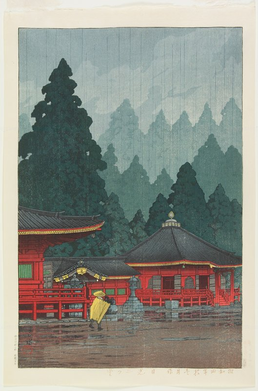 figure in yellow with yellow hat walking towards red temple buildings in the rain; pine trees in background