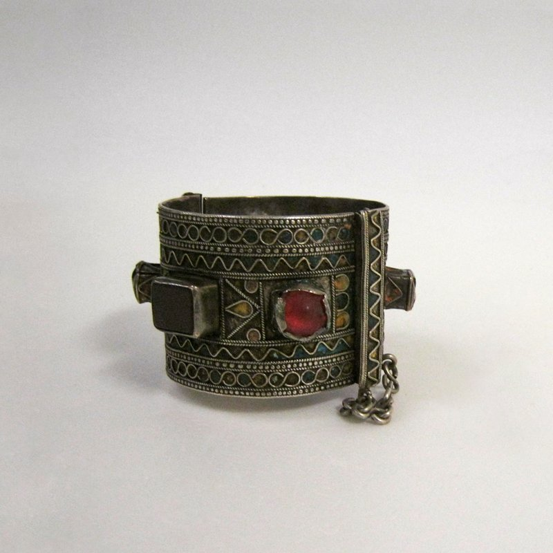 cuff bracelet with hinge and pin closure; six large inset pieces of glass (red, amber, pink, green); bands with scrolling silver wire designs and enamel inlay in blue, yellow and orange