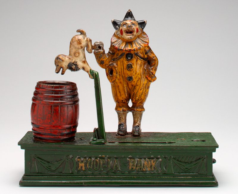 "clown in yellow costume and black 3 coned hat holds right hand up from elbow; dog on lever; red barrel; all things raised on green pedestal; ""HOOP_LA BANK"" on front side of pedestal"