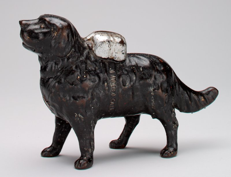 black dog with silver bag on back tied around stomach by silver strap